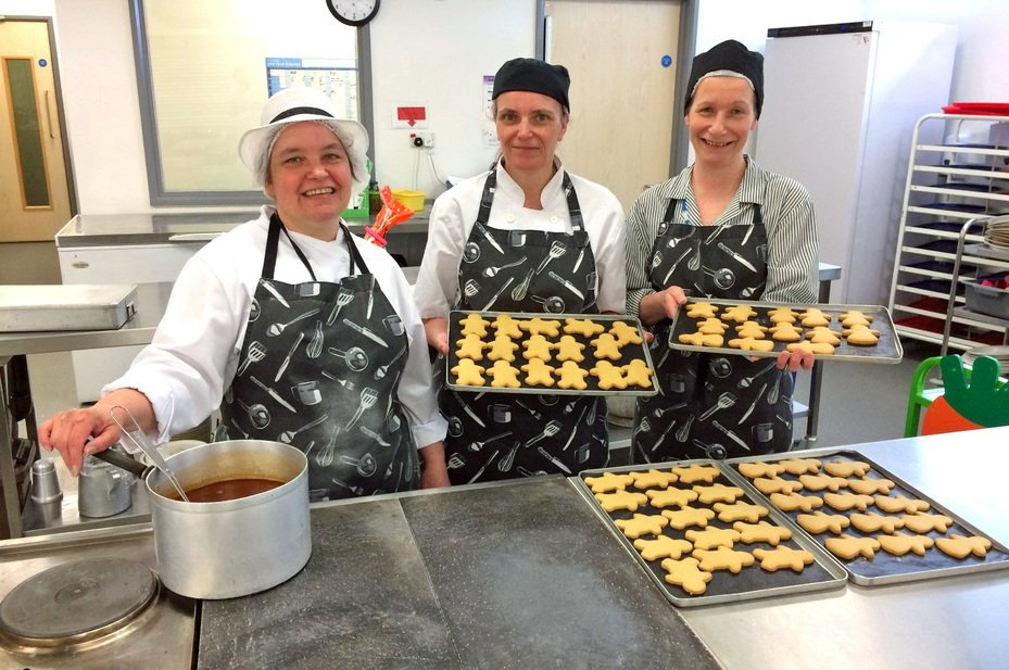 Catering staff serving food in the school kitchen