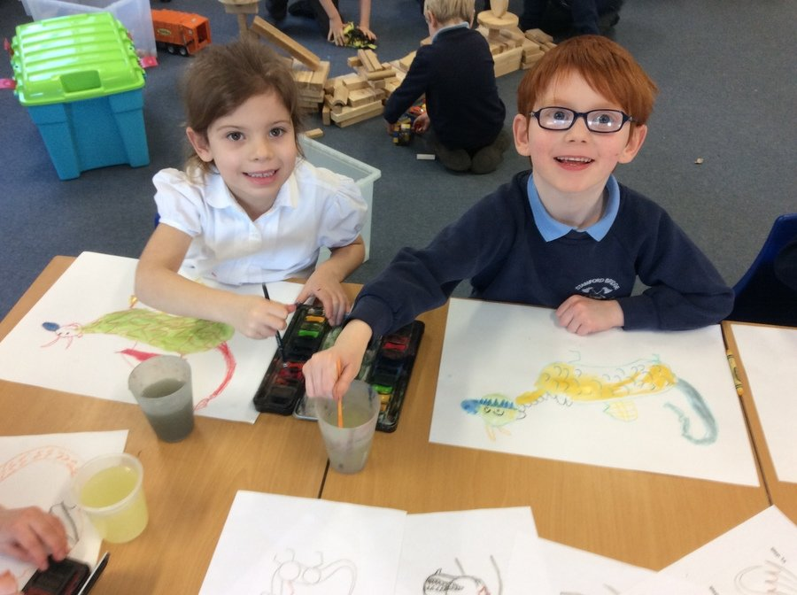 Working carefully on wax crayon and watercolour dragons. Aren't they beautiful!
