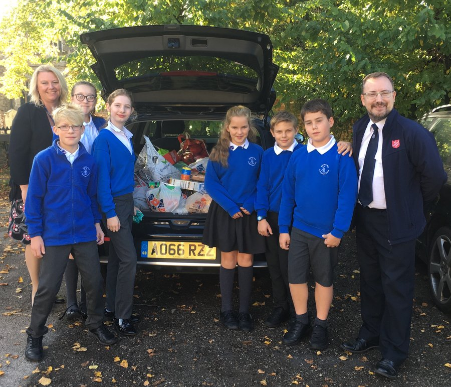 Pupils at our Harvest Festival service help gather donations for the Salvation Army