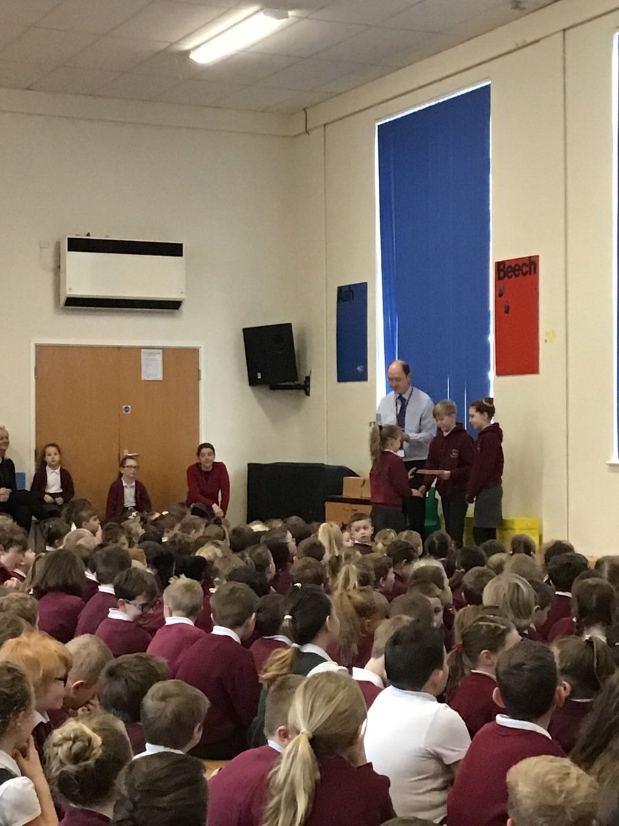 Violet and Zak help to distribute certificates in our Friday Celebration Assembly