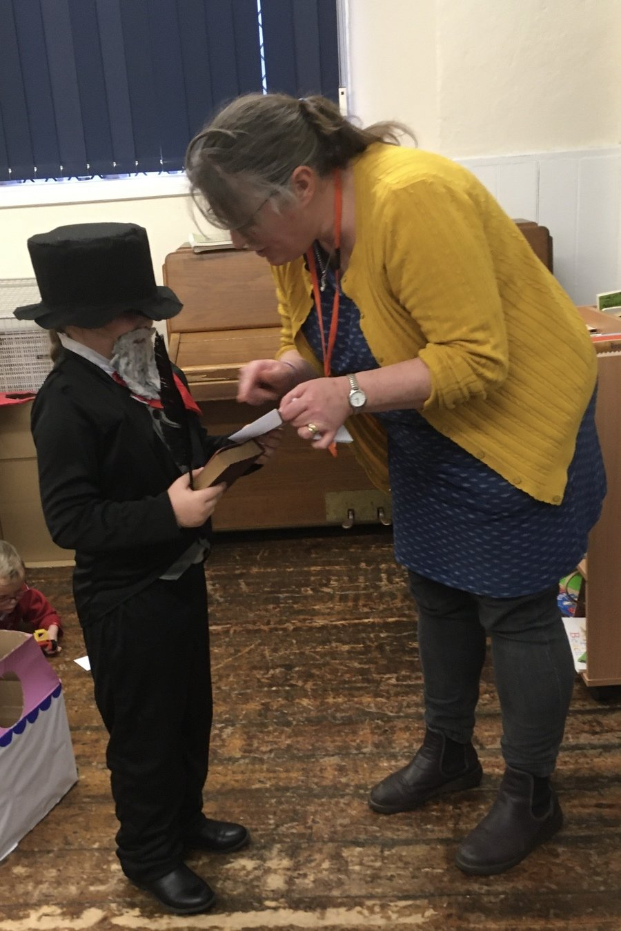 Mrs Pettis from the PFA is presenting Poppy in Y3 with her World Book Day Winning prize for dressing up as Charles Dickens