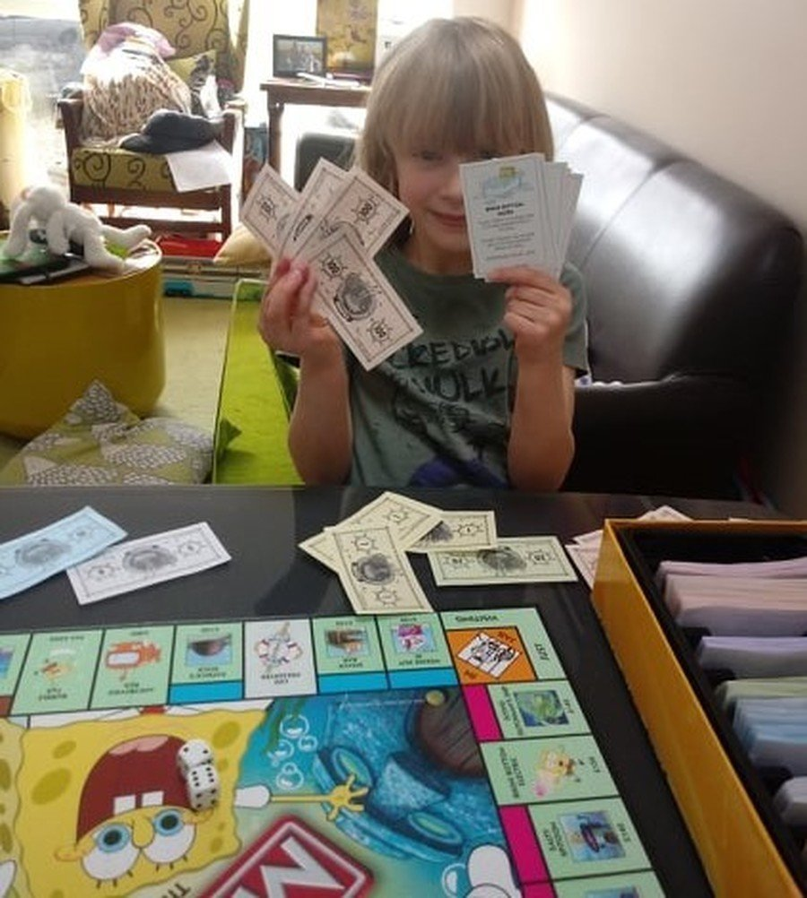 Ivy doing maths work by playing banker at Monopoly.