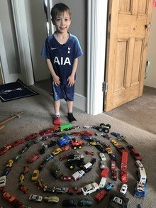 Leo creating art with his toy cars