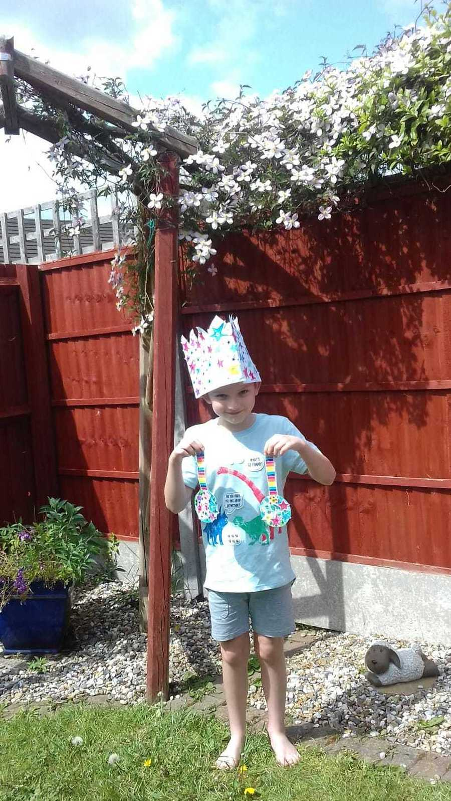 A child in year 4 showing his crown and medals he has created.