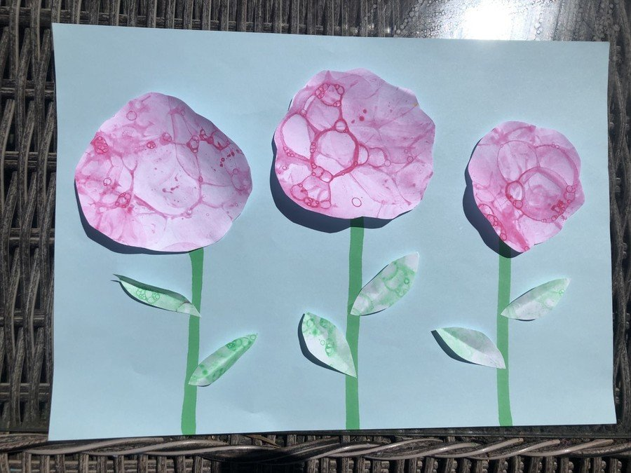 The pink and green paintings were cut up and placed on a blue background to create flowers