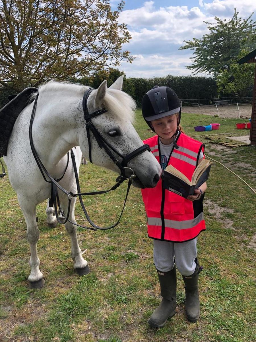 Heidi #GetCaughtReading with her horse. She looks like she's really focused on the story that she is  being read.