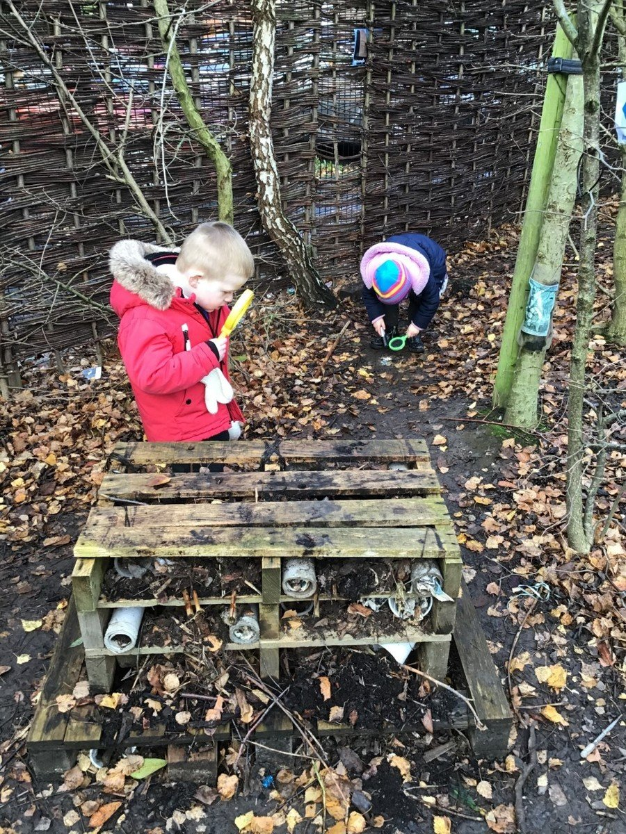 Exploring  the bug hotel and looking between the stones, logs, leaves and bushes with their magnifying glasses to see what minibeasts they can find.