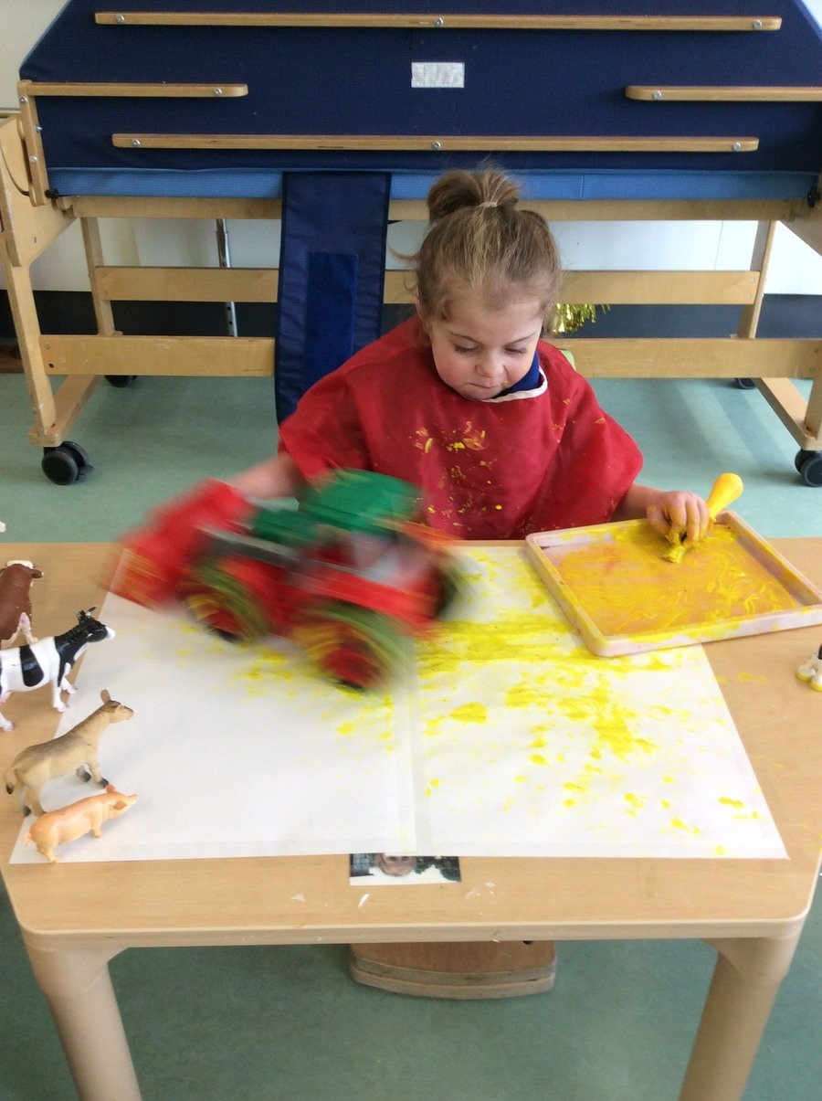 "M really showed enjoyment during our ""farmers"" week. She loved making marks in the paint using the tractor, she was able to independently push the tractor around in the paint, after painting the wheels with her brush! Amazing work M :)"