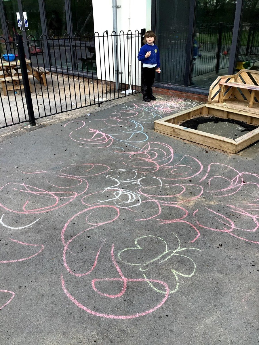 """S watched as a picture of a butterfly picture was drawn using chunky chalks. The writing pattern """"curved"""" was verbally said out loud as the wings were drawn. S was then handed a chunky chalk. He independently drew curved lines resembling the letter C formation onto the floor. S repeated this writing pattern on several occasions, until a large area of the playground floor was covered. S demonstrated a good understanding of the writing pattern, by only creating curved lines and circles."""