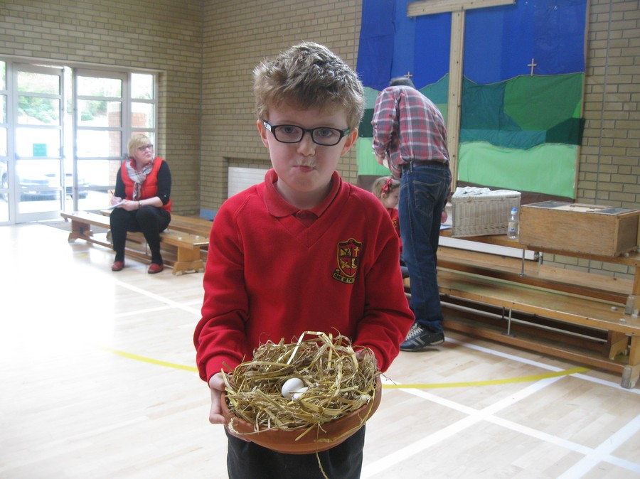 Ethan holds a clay dish with two eggs newly laid by one of Joe's pigeons.