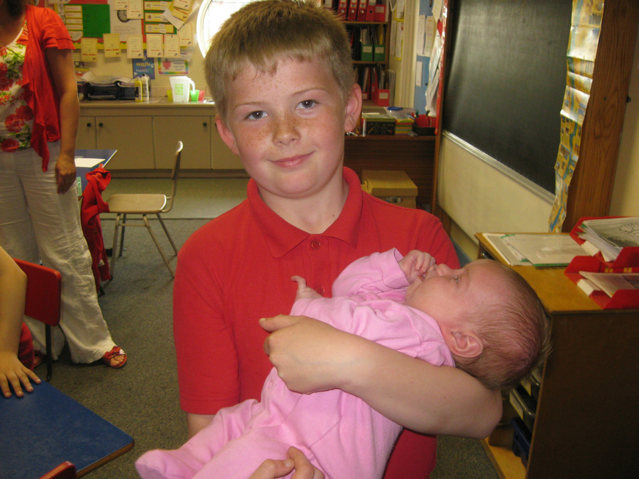 Lewis proudly holds his baby sister Liela