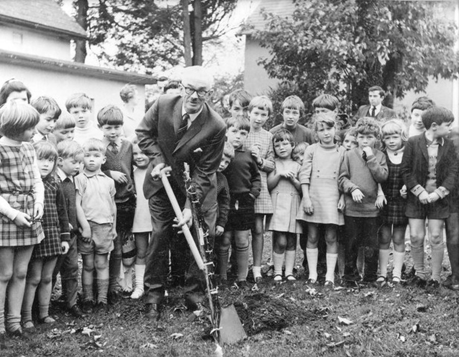 Mr Gillespie plants a tree to mark his retirement. The present Chair of the School Board of Governors (Mrs Valerie Crawford (nee Armstrong) as a pupil witnesses the event (second right)