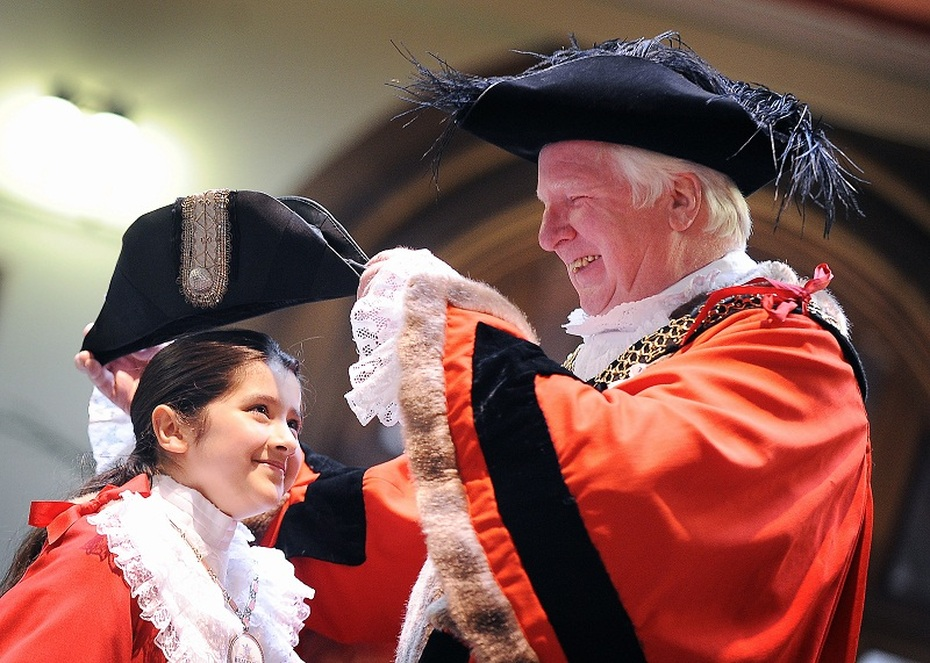 Lord Mayor Councillor, Dale Smith helps the mini Lord Mayor for the day, Ruqayyah Rauf, from Girlington Primary School, with her robes at the start of Old People's Week in City Hall