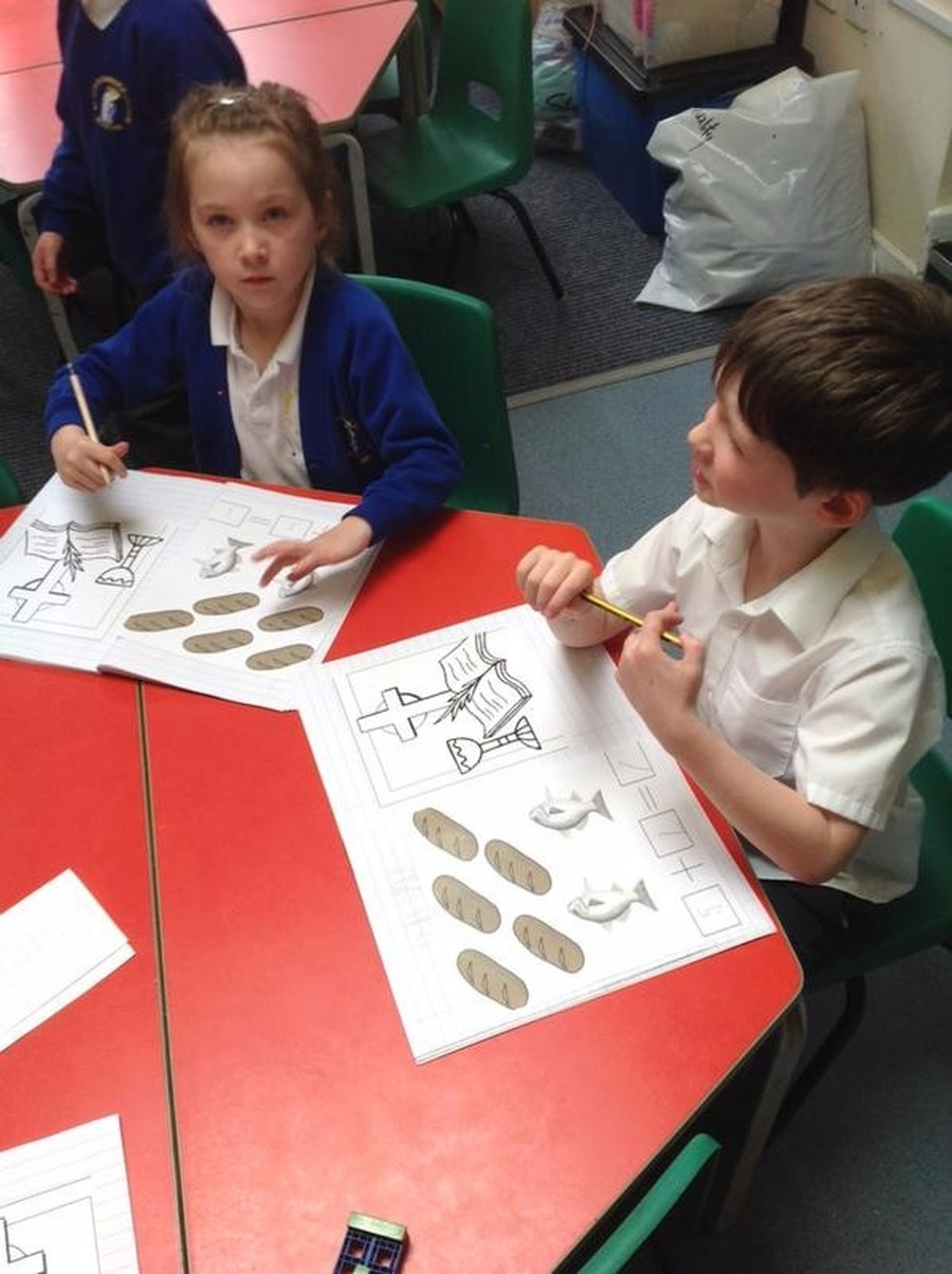 Children in Reception writing the sentence 'He is Risen' during their RE lesson.