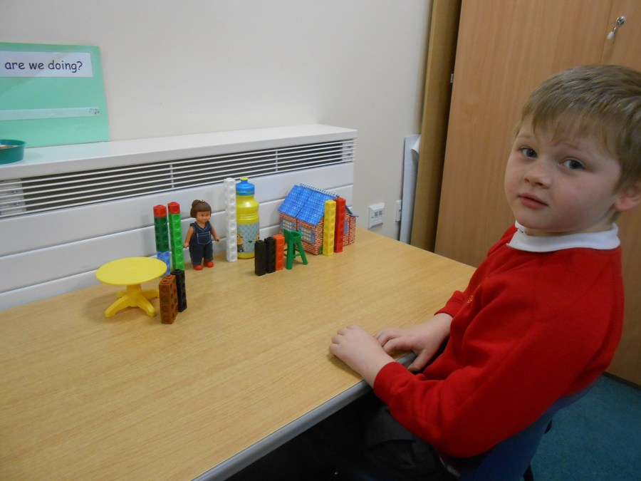 "Reegan has been measuring using non-standard units. He has made towers ""as tall as"" the objects on the table. Well done Reegan."