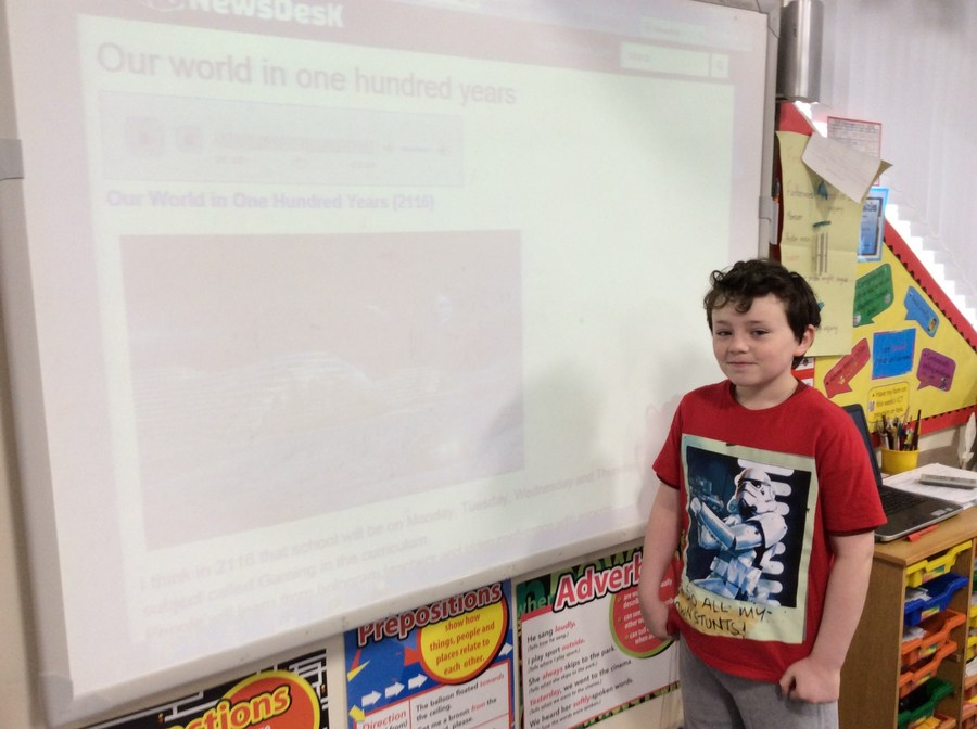 Noah proudly displays his news report, featured on the Newsdesk,  on the big screen - 'Our World in 100 Years'