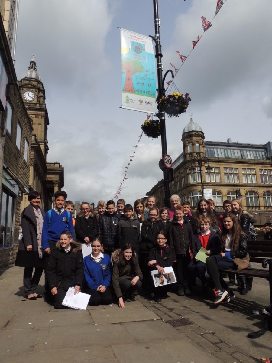 Cluster Council members, Councillor Elliott and Cluster Leader Helen Kerr pictured in Queen Street with one of the banners designed by a school in our Cluster.
