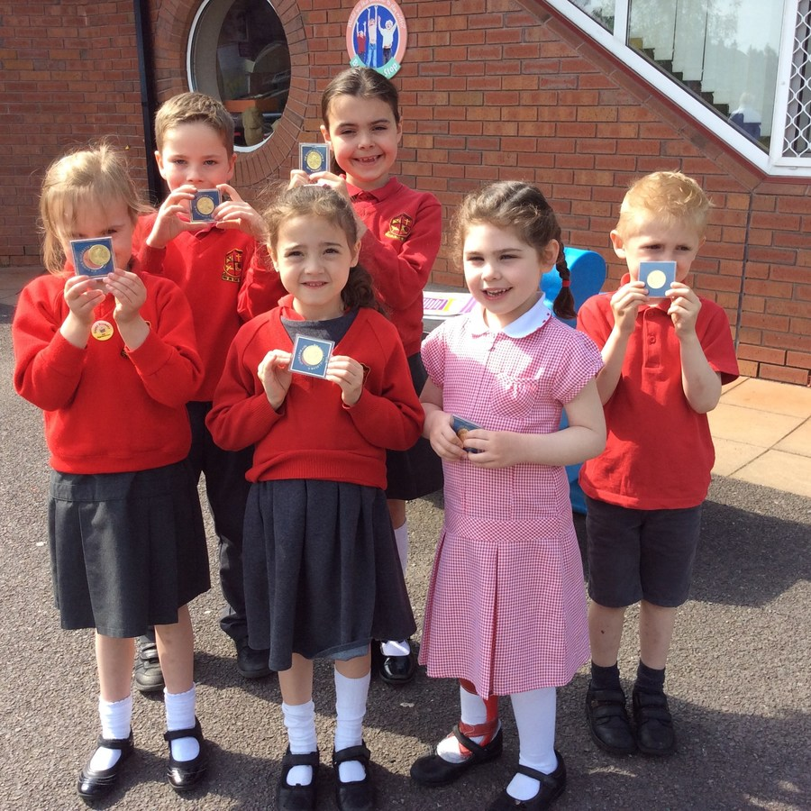 Smiling faces from pupils in P.1-P.3 display the Queen's 90th birthday coins.