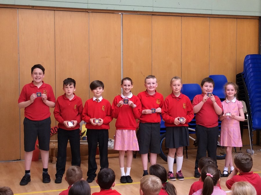 Children from P.4-P.7 who won celebration coins for the Queen's 90th birthday.