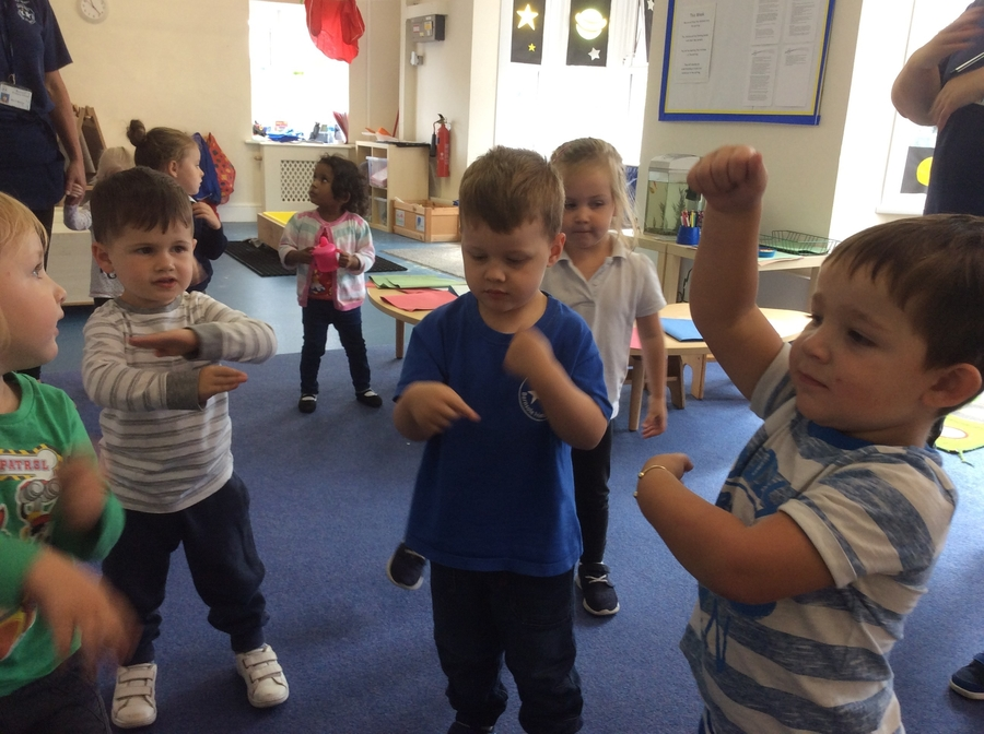 The children were singing and dancing to the wheels on the us. Learning songs helps to develop the children's listening and attention skills. The actions support memory.