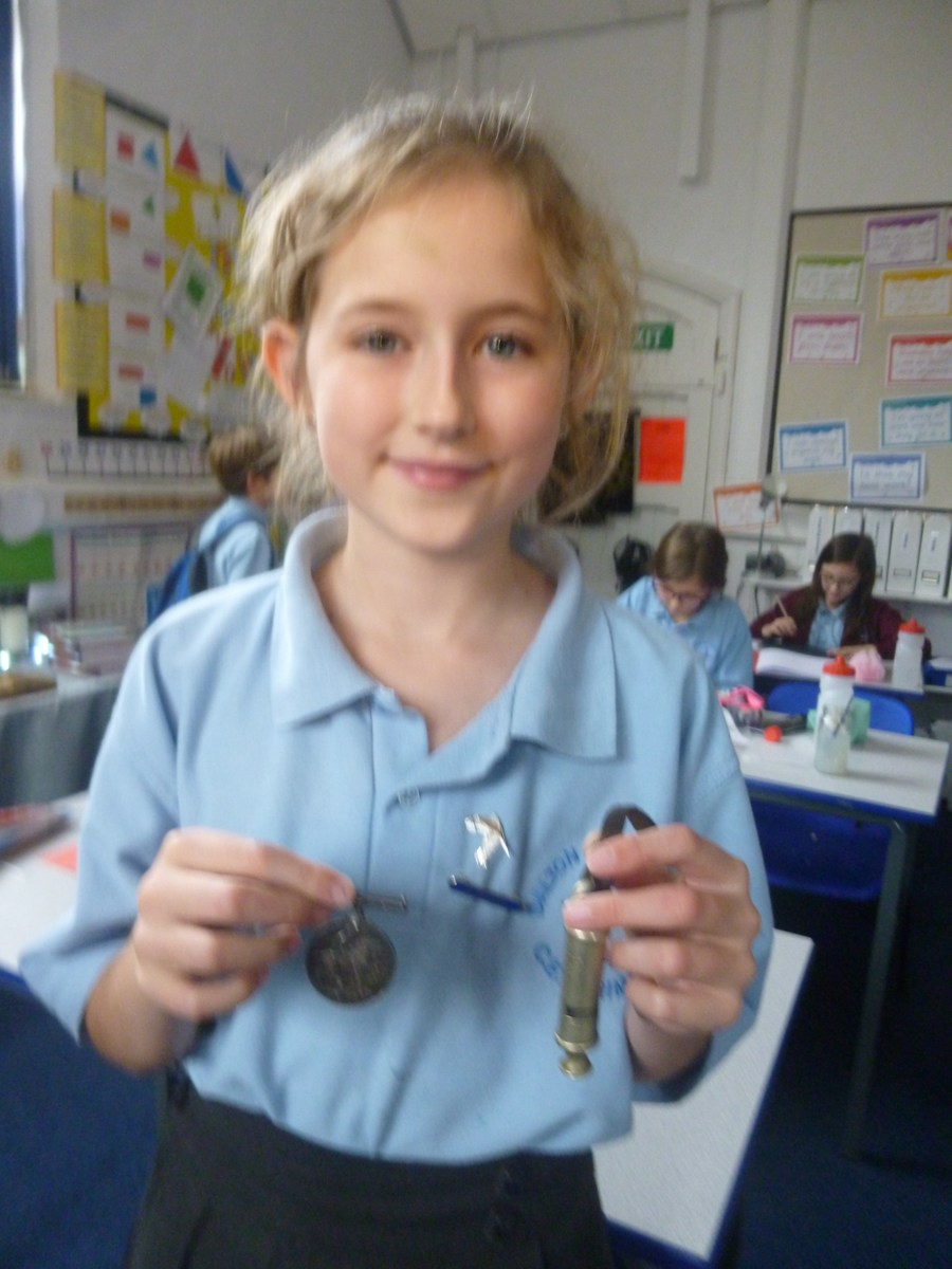 Harriet showing her Grandfather's trench whistle and medal.