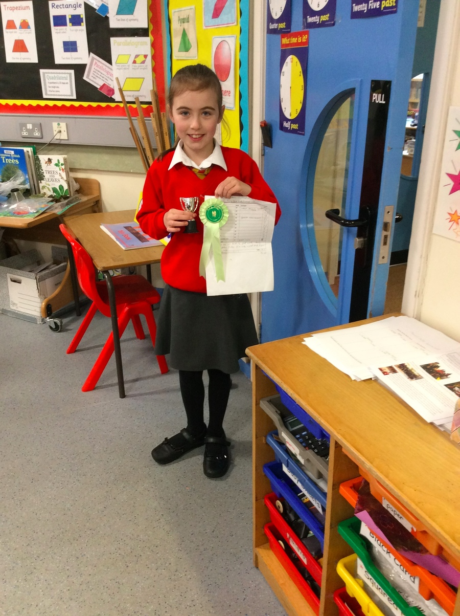 Lucy proudly displays her cup and rosette which she won in a recent horse riding competition