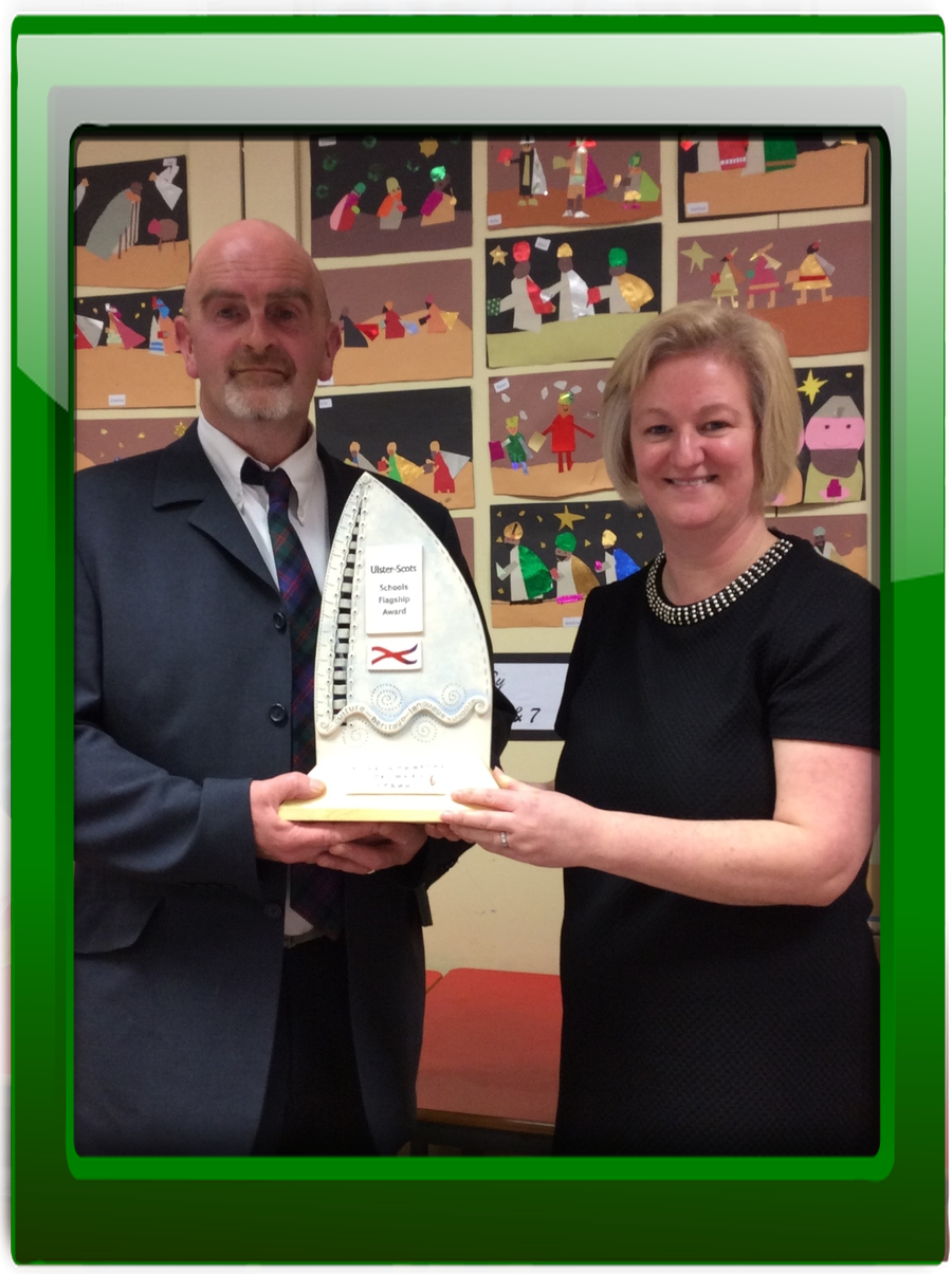 Ms Wilson receives the award from Mr Gary Blair, Ulster-Scots Agency, following the Keystage 2 children's performance of Dan Gordon's play 'The Boat Factory '.