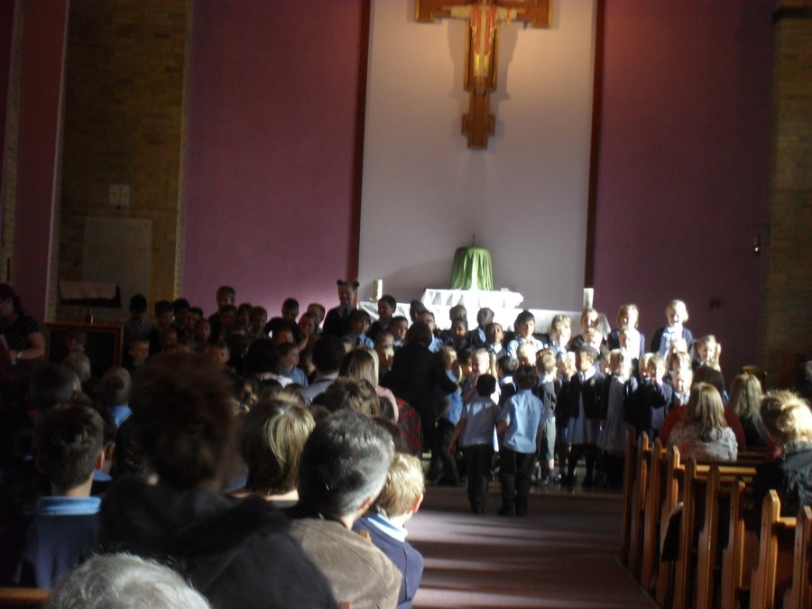 Key stage one singing at the Harvest Liturgy at Church