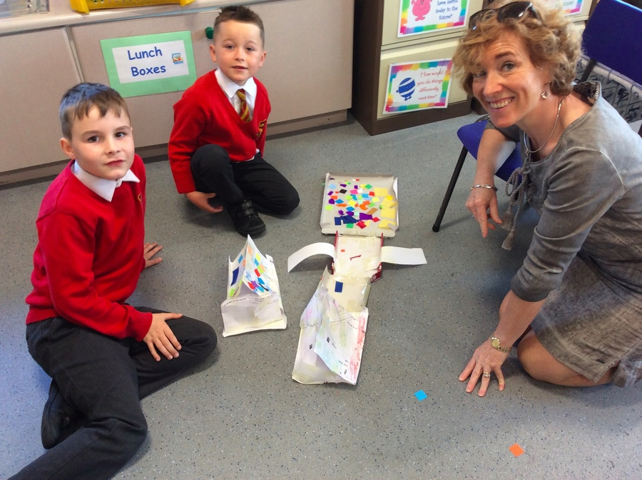 Jordan and Alfie show Mrs Morrow their boats.