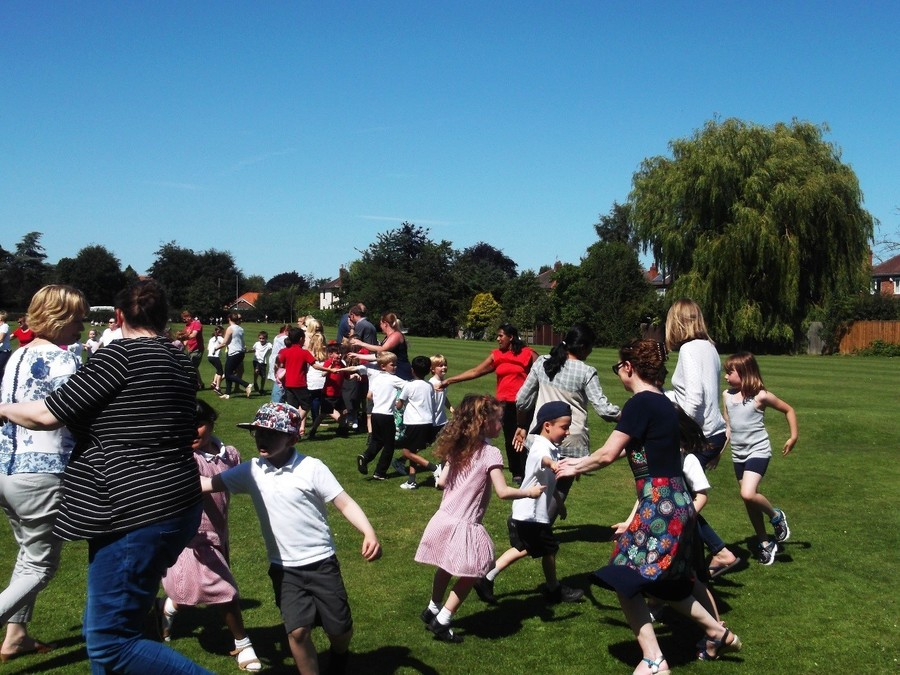 Parents, grandparents, children and staff dancing in the sunshine at our end of year ceilidh